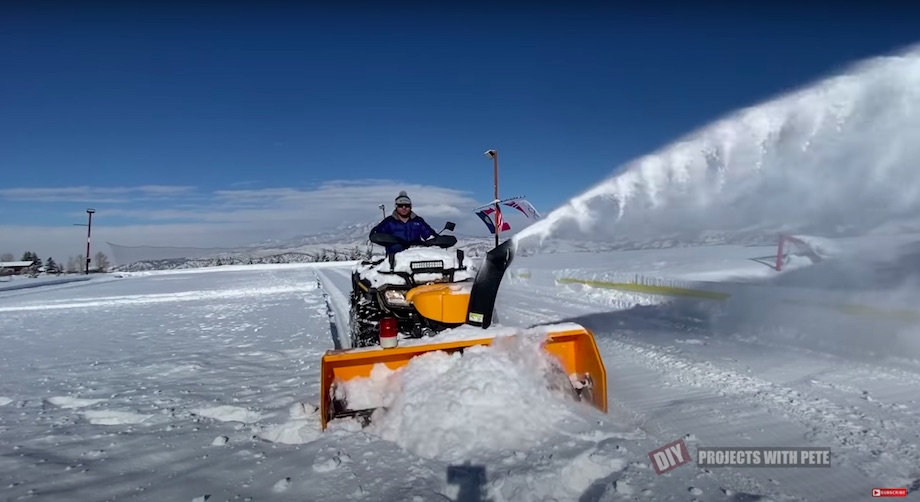 Snowblower mounted to the front of an ATV 4-wheeler